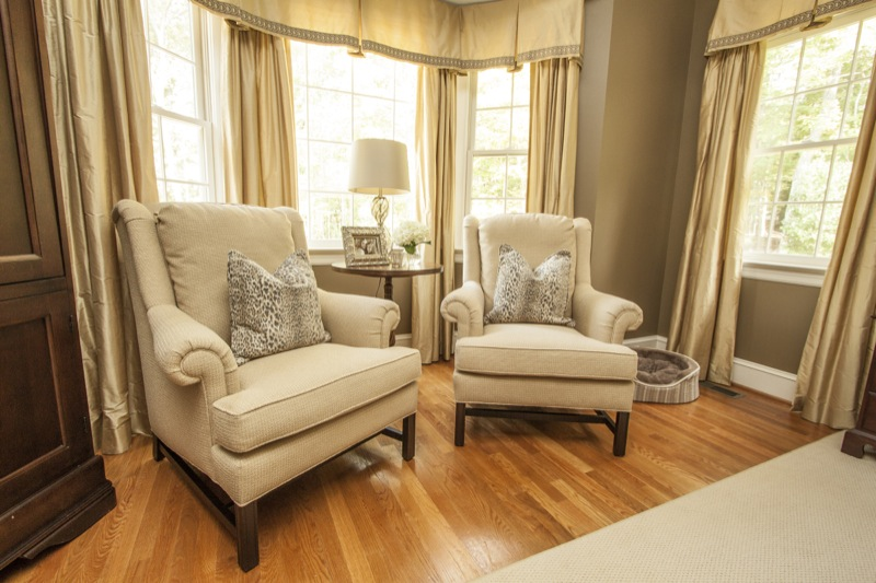 A pair of custom armchairs tuck into the gorgeous sitting area. If you're looking for inspiration on dressing a bay window this photo is for you.