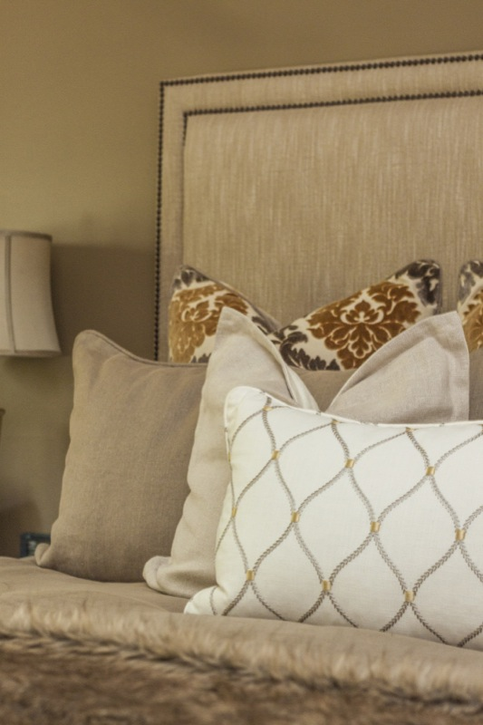 Custom pillows and a hand-crafted headboard complete the look in this gorgeous golden bedroom.
